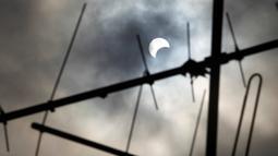 Pemandangan gerhana matahari parsial yang terlihat di langit Abidjan, Pantai Gading, Kamis (1/9). Pemandangan tersebut merupakan bagian dari fenomena gerhana matahari cincin dengan titik 'great eclipse' di Tanzania. (REUTERS/Luc Gnago)