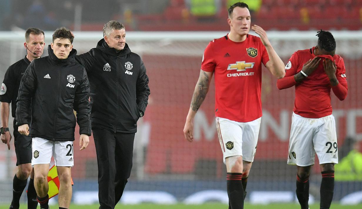Manajer Manchester United, Ole Gunnar Solskjaer bersama timnya, Daniel James, Phil Jones dan Aaron Wan-Bissaka meninggalkan lapangan setelah laga lanjutan Liga Inggris kontra Burnley di Old Trafford, Rabu (23/1/2020). MU tidak berdaya di kandang sendiri usai takluk 0-2 dari Burnley. (Paul ELLIS/AFP)