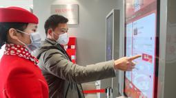 Wisatawan membeli tiket dengan mesin penjual tiket otomatis di Shanghai Oriental Pearl Tower, Shanghai, China, Kamis (12/3/2020). Shanghai Oriental Pearl Tower, Shanghai Jinmao Tower, dan Shanghai Tower sudah menerima wisatawan mulai 12 Maret 2020. (Xinhua/Ding Ting)