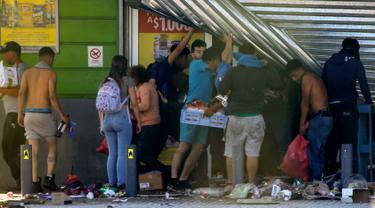 Warga menjarah sebuah supermarket di Puente Alto, wilayah metropolitan Santiago, Chile, Minggu (20/10/2019). Bentrokan pecah di Santiago setelah dua orang tewas ketika sebuah supermarket dibakar ketika protes terhadap kondisi ekonomi dan ketidaksetaraan sosial. (DRAGOMIR YANKOVIC/ATON CHILE/AFP)