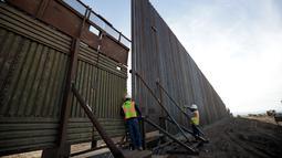 Pekerja melihat di antara pagar perbatasan Amerika Serikat (AS) dengan Meksiko di Calexico, California, AS, Minggu (5/3). Pembangunan tembok pembatas di area ini sudah direncanakan sejak zaman Barack Obama tahun 2009. (AP Photo/Gregory Bull)
