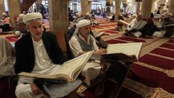 Sejumlah pria membaca Al-Quran selama bulan Ramadan di Masjid Agung Sanaa, Yaman, Minggu (26/4/2020). Kaligrafi dan dekorasi merupakan kekhasan Masjid Agung Sanaa. (Mohammed HUWAIS/AFP)