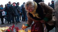 Warga meletakan meletekan lilin di dekat lokasi ledakan bom di stasiun kereta bawah tanah St. Petersburg, Senin (3/4). Dikabarkan kejadian tersebut menewaskan 10 orang dan menghancurkan sebuah gerbong kereta. (AP Photo / Dmitri Lovetsky)