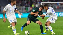 Striker Italia, Federico Chiesa, berusaha melewati bek Yunani, Kostas Stafylidis, pada laga Kualifikasi Piala Eropa 2020 di Stadion Olimpico, Roma, Sabtu (12/10). Italia menang 2-1 atas Yunani. (AFP/Alberto Pizzoli)