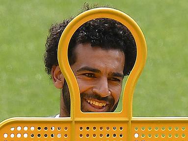 Gelandang Liverpool asal Mesir Mohamed Salah tersenyum saat mengikuti sesi pelatihan di stadion Anfield, Inggris (21/5). Liverpool akan bertanding melawan wakil Spanyol, Real Madrid pada babak Final Liga Champions. (AFP Photo/Paul Ellis)