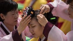Seorang pelajar mempersiapkan diri sebelum mengikuti upacara Coming of Age Day di Namsan Hanok Village, Seoul, Senin (15/5). Upacara Hari Kedewasaan adalah hari libur resmi untuk menghormati siapa saja yang baru menginjak usia 20 tahun. (Ed JONES/AFP)