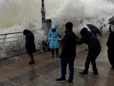 Warga memfoto ombak besar yang menghantam tembok di Beirut, Lebanon (6/1). Badai kuat di Lebanon membawa suhu dingin dan salju ke pegunungan dan hujan lebat, angin kencang melanda pantai bagian dari negara Mediterania tersebut. (AP Photo/Bilal Hussein)