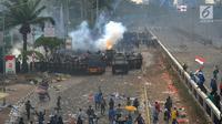 Polisi menembakkan gas air mata ke arah mahasiswa saat demonstrasi menolak pengesahan RUU KUHP dan revisi UU KPK di depan Gedung DPR, Jakarta, Selasa (24/9/2019). Polisi menghalau mahasiswa yang berusaha masuk ke area Gedung DPR. (merdeka.com/Arie Basuki)