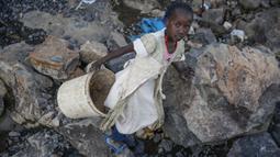 Irene Wanzila, 10, membawa seember batu pecah setelah ibunya yang kehilangan pekerjaan sebagai petugas kebersihan di sekolah swasta ketika pembatasan pandemi virus corona diberlakukan, di tambang Kayole di Nairobi, Kenya, 29 September 2020.  (AP Photo/Brian Inganga)