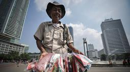 Pedagang parasut mainan menjajakan dagangannya di kawasan Bundaran HI, Jakarta, Minggu (22/3/2015).  Seiring dengan perkembangan zaman dan modernisasi, permainan tradisional kini mulai tergantikan. (Liputan6.com/Faizal Fanani)