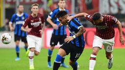 Striker Inter Milan, Lautaro Martinez, berusaha melewati bek AC Milan, Mateo Musacchio, pada laga Serie A di Stadion San Siro, Milan, Sabtu (21/9). Milan kalah 0-2 dari Inter. (AFP/Miguel Medina)