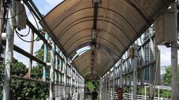 Pejalan kaki melintasi jembatan penyeberangan orang (JPO) di Jalan Sudirman, Jakarta, Jumat (27/4). Nantinya, JPO sepanjang Jalan Sudirman hingga Thamrin akan direvitalisasi dengan tema Asian Games. (Liputan6.com/Arya Manggala)