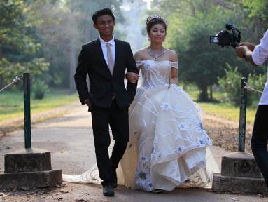Sepasang pengantin baru melakukan foto pernikahan mereka di kompleks kuil Angkor Wat, sebuah candi ikonik dan bersejarah di Kamboja, 14 Maret 2018. Candi ini adalah jantung dan jiwa Kamboja serta menjadi kebangaan nasional. (AP Photo/Heng Sinith)
