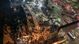 Tim penyelamat mencari korban selamat di puing-puing sebuah hotel yang runtuh di Quanzhou, China, Sabtu (7/3/2020). Sekitar 70 orang terjebak di hotel Xinjia yang akhir-akhir ini digunakan sebagai tempat karantina untuk orang-orang yang berhubungan dengan pasien virus corona. (STR/AFP)
