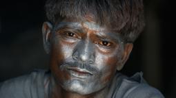 """Wajah seorang pekerja dipenuhi bubuk mesiu untuk membuat petasan, di sebuah pabrik pinggiran  Ahmadabad, Senin (22/10). Permintaan petasan di India semakin meningkat jelang perayaan Festival """"Cahaya"""" Diwali bagi umat Hindu. (AP/Ajit Solanki)"""