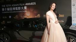 Aktris asal Taiwan, Shu Qi tersenyum disamping mobil mewah saat menghadiri malam penganugerahan Asian Film Awards 2016 di Macau, China, Asian Film Awards diadakan setiap tahun sejak 2007. (AFP/ISAAC LAWRENCE)