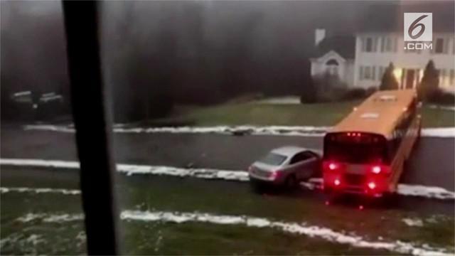 Kondisi jalan yang membeku dan licin akibat cuaca dingin membuat sebuah bus sekolah  kehilangan kendali.