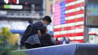 Seorang pria dan anaknya beristirahat di Times Square, New York, Amerika Serikat (AS), 9 November 2020. Menurut Center for Systems Science and Engineering (CSSE) di Universitas Johns Hopkins, jumlah kumulatif kasus COVID-19 di AS mencapai 10 juta kasus pada Senin (9/11). (Xinhua/Wang Ying)