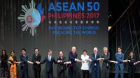 Presiden AS, Donald Trump dan para pemimpin lainnya melakukan salaman khas ASEAN di penghujung upacara pembukaan KTT ASEAN di Manila, Filipina, Senin (13/11). Trump sempat kesulitan menempatkan tangannya di posisi yang pas. (AP/Andrew Harnik)