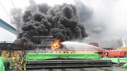 Petugas pemadam kebakaran menyeprotkan air ke arah kapal kargo yang terbakar di pelabuhan Ulsan, di pantai tenggara Korea Selatan (28/9/2019). Menurut pihak berwenang, sembilan pelaut terluka setelah kebakaran terjadi di kapal kargo dan menyebar ke kapal lainnya. (AFP/Yonhap)