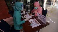 Calon penumpang melakukan pendaftaran untuk mendapatkan voucher tiket kereta api (KA) jarak jauh secara gratis di Stasiun Gambir, Jakarta, Sabtu (7/11/2020). Penumpang yang berhak mendapatkan voucher adalah guru TK sampai SMA sederajat dan tenaga kesehatan kecuali dokter. (merdeka.com/Imam Buhori)