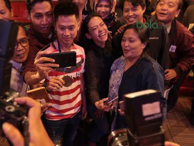 Kevin Sanjaya mengikuti foto elfie bersama fans dan wartawan di Galeri Indonesia Kaya, Grand Indonesia, Jakarta (28/3/2018). Kevin menerima deposito sebesar Rp 200 juta. (Bola.com/Nick Hanoatubun)