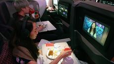 Pengunjung menonton film sembari menikmati makanan di kelas bisnis selama makan siang perdana di Restaurant A380 @Changi di atas pesawat Airbus A380, di Bandara Internasional Changi, 24 Oktober 2020. Singapore Airlines mengubah salah satu pesawatnya menjadi sebuah restoran mewah. (ROSLAN RAHMAN/AFP)