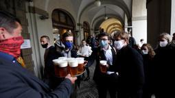 Orang-orang mengantre untuk minum bir di teras restoran di Praha, Republik Ceko, Senin, (11/5/2020). Republik Ceko mengambil langkah normal di tengah pandemi coronavirus dengan melonggarkan lebih banyak pembatasan yang diadopsi oleh pemerintah untuk menampungnya. (AP/Petr David Josek)