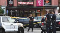 Aparat kepolisian berjaga di luar toko pakaian Marathon Clothing setelah insiden penembakan rapper kenamaan Nipsey Husle di Los Angeles, Minggu (31/3). Rapper yang masuk nominasi Grammy Awards 2019 itu sempat dilarikan ke rumah sakit, tetapi nyawanya tida