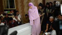 Istri gitaris grup band Seventeen Herman Sikumbang, Juliana Muhtar menangis saat menerima kedatangan jenazah suami di rumah duka di Pancoran, Jakarta, Senin (24/12). Herman menjadi korban tsunami Anyer. (Kapanlagi.com/Bayu Herdianto)