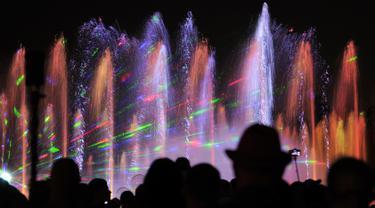 Pengunjung menyaksikan air mancur menari pada awal musim semi di taman Warsawa, Polandia, 1 Mei 2018. Atraksi ini memadukan teknologi pertunjukan lampu laser tiga dimensi, semburan menara api, layar air digital serta pancuran air. (AP/Alik Keplicz)