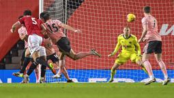Pemain Manchester United Harry Maguire (kiri) mencetak gol ke gawang Sheffield United pada pertandingan Liga Inggris di Old Trafford, Manchester, Inggris, Rabu (27/1/2021). Sheffield United menang 2-1. (AP Photo/Laurence Griffiths,Pool)