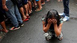 Salah satu anggota keluarga menangis saat melihat tubuh Nora Acielo tewas ditembak orang tak dikenal di Manila, Filipina, Kamis (8/12). Acielo ditembak saat sedang mengantarkan kedua anaknya berangkat sekolah. (REUTERS/Erik De Castro)