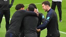 Gelandang Inggris, Raheem Sterling (tengah) tertawa saat ditangkap dalam pertandingan Kabaddi selama sesi pelatihan tim  di Staplewood Campus di southampton, Inggris  (9/9/2019). Inggris akan bertanding melawan Kosovo pada grup A Kualifikasi Euro 2020 di Stadion Saint Mary. (AFP Photo/Glyn Kirk)