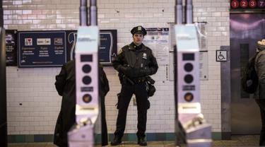 Petugas kepolisian New York berjaga di pintu masuk stasiun kereta bawah tanah Times Square saat jam sibuk malam di New York City, Senin (11/12). Sebelumnya ledakan bom terjadi di terminal bawah tanah kawasan Manhattan. (Drew Angerer/Getty Images/AFP)