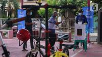 Warga bersiap memasukkan surat suara usai mencoblos dalam Pilkada 2020 di TPS 23 Pondok Jagung Timur, Tangerang Selatan, Rabu (9/12/2020). TPS Pilkada Tangerang Selatan (Tangsel) itu menggunakan tema hobi dimana petugasnya mengenakan pakaian untuk bersepeda. (Liputan6.com/Angga Yuniar)