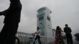 Orang-orang melewati gedung pencakar langit Pangu Plaza di seberang Stadion Olimpiade Bird's Nest, Beijing, Selasa (20/7/2019). Gedung yang pernah masuk dalam film Transformers: Age of Extinction itu terjual dalam lelang online dengan harga 734 juta USD atau sekitar Rp10,5 triliun. (GREG BAKER/AFP)