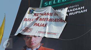 Sebuah reklame bergambar Dude Harlino tertutup spanduk di Kawasan Kebayoran Lama, Jakarta, Kamis (23/2). Reklame tersebut terkena razia oleh Satpol PP dan Dinas BP2T karena belum membayar pajak. (Liputan6.com/Gempur M Surya)