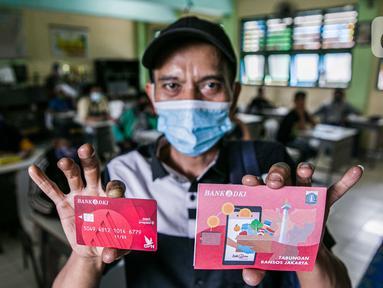 Warga menunjukkan buku tabungan dan ATM usai mengambil Bantuan Sosial Tunai (BST) di SMAN 111, Jakarta, Selasa (19/1/2021). Pemprov DKI Jakarta menyalurkan BST sebesar Rp 300 ribu kepada 1.055.216 KK mulai Januari hingga April 2021. (Liputan6.com/Faizal Fanani)