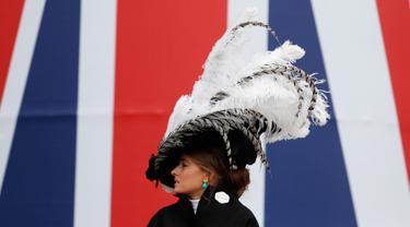 Seorang wanita mengenakan topi atau fascinator unik bermotif bulu melintas di depan bendera Union Jack saat menghadiri ajang pacuan kuda Royal Ascot di Ascot, Inggris, Selasa (18/6/2019). Royal Ascot menjadi ajang bagi wanita Inggris untuk tampil dengan fascinator unik. (AP Photo/Alastair Grant)