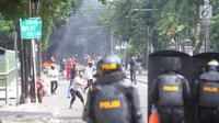 Pengunjuk rasa melemparkan batu ke arah petugas polisi selama bentrokan sebelum terjadi pembakaran bis milik Brimob di kawasan Tanah Abang,  Jakarta, Rabu (22/5/2019). (merdeka.com/Arie Basuki)