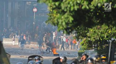 Bentrok antara polisi dan massa aksi di kawasan Tanah Abang, Jakarta, Rabu (22/5/2019).  Beberapa kelompok massa menggunakan benda-benda keras hingga mercon untuk menahan laju petugas keamanan. (Liputan6.com/Herman Zakharia)