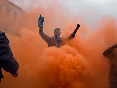 Peserta bermandikan tepung berwarna saat mereka mengikuti perang tepung terigu di kota pelabuhan Galaxidi, Yunani (19/2). Perang tepung yang berwarna-warni ini menandai akhir musim karnaval. (AP/Petros Giannakouris)