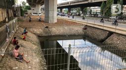 Sejumlah warga memancing ikan di kubangan yang berada di Jalan DI Panjaitan, Jatinegara, Jakarta, Selasa (16/6/2020). Meski telah dipagari, sejumlah warga tetap memancing ikan di lokasi yang merupakan saluran pembuangan tersebut. (Liputan6.com/Immanuel Antonius)