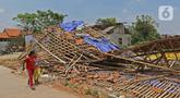 Anak-anak melintasi puing-puing bangunan rumah yang rusak diterjang angin puting beliung di Kaliabang Tengah, Kota Bekasi, Sabtu (24/10/2020). Menurut Badan Penanggulangan Bencana Daerah (BPBD) sebanyak 159 rumah terdampak puting beliung yang terjadi Jumat siang. (Liputan6.com/Herman Zakharia)