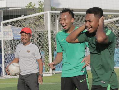 Pemain Timnas Indonesia U-22, Rafi Syarahil dan Awan Setho, tertawa saat latihan di Lapangan AUPP, Phnom Penh, Selasa (19/2). Latihan ini persiapan jelang laga Piala AFF U-22 melawan Malaysia. (Bola.com/Zulfirdaus Harahap)