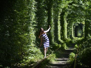 Seorang gadis berjalan di sepanjang bekas rel kereta api atau disebut 'Tunnel of Love' yang dikelilingi pohon dekat desa Ukraina Klevan, Rivno, (6/8). Terowongan cinta yang panjangnya sekitar lima km adalah fenomena botani. (AFP Photo/Sergei Supinsky)