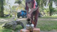 Saifudin menuangkan nira ke dalam ceret untuk direbus bersama bubuk kopi di sanggar seni dan budaya GMB, Desa Jambi Tulo, Marosebo, Kabupaten Muaro Jambi, Sabtu (13/7/2019). (Liputan6.com/ Gresi Plamanto)