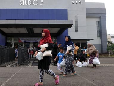 Warga membawa Paket  Sembako Murah oleh PT Indosiar Visual Mandiri  di Studio 5 Indosiar, Jakarta, (10/6). Sebanyak 500 paket sembako murah seharga Rp 30 ribu per paket untuk 500 Kepala Keluarga (KK). (Liputan6.com/Johan Tallo)