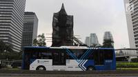 Bus Transjakarta melintas di samping Patung Jenderal Sudirman di Jakarta, Senin (16/4). Perbaikan Patung tersebut untuk merawat agar patung tetap dalam kondisi baik dan tidak terjadi korosi karena faktor cuaca. (Liputan6.com/Arya Manggala)
